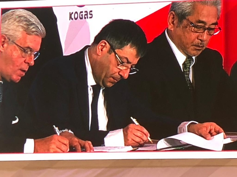 Pierre Bechelany (centre), Fluor's president of pipelines and LNG, signs the contract.